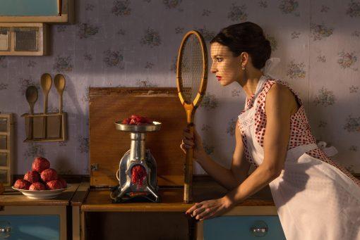 Postkarte the Game von Horst Kistner: Frau mit Tennisschläger in der Küche