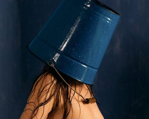 Frau mit blauem Eimer auf dem Kopf