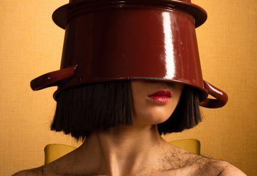 Detail einer Fotografie: Frau mit einem Eimer auf dem Kopf.