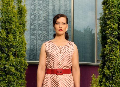 Frau mit rot gepunktetem Kleid und strengem Blick.