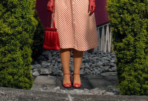 Frau mit rot gepunktetem Kleid und roter Tasche.