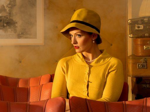 Porträt einer Frau mit gelben Hut und gelben Sakko und rot geschminkten Lippen.
