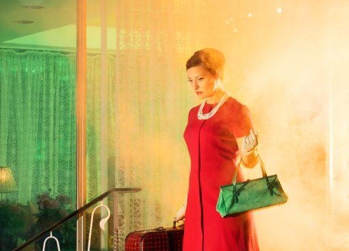 Frau mit rotem Kleid im Gegenlicht eines Feuers.