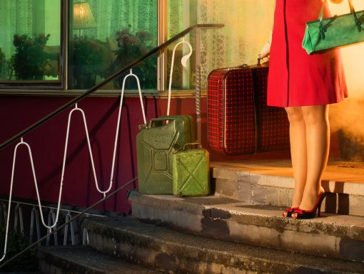 Detail einer Fotografie mit den Beinen einer Frau und Benzinkanistern.