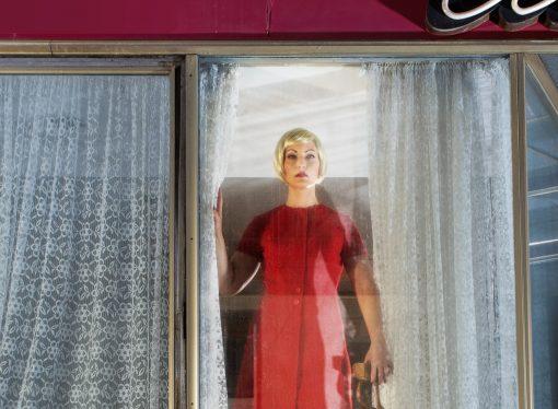 Bewegungslose Frau hinter einem Fenster