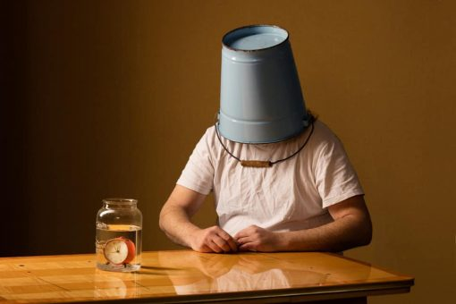 Coronapostkarte Kunst und Corona von Horst Kistner zeigt einen Mann mit Eimer über dem Kopf wartend am Tisch sitzen