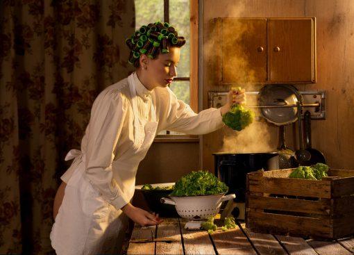 Horst Kistner | Postkarte | Yearning for Greens - Auf der Postkarte von Horst Kistner mit dem Titel Yearning for Greens ist eine Frau mit Brokkoli zu sehen
