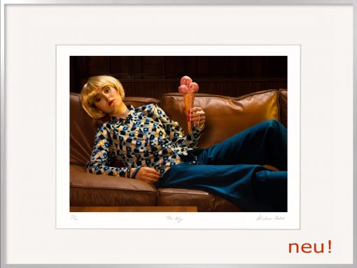 Horst Kistner The Wig Fotografie zeigt eine auf dem Sofa liegende Frau mit einem zerfließenden Eis in der Hand und einer blonden Perücke.